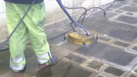 Un homme commence à nettoyer des trottoirs recouverts de crasse – c'est très agréable de les voir à l'oeuvre