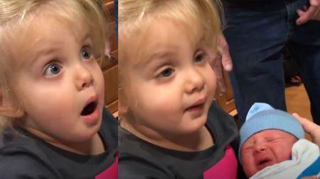 Une fille essaie d'embrasser son petit frère nouveau-né. Mais sa réaction – son visage en dit long