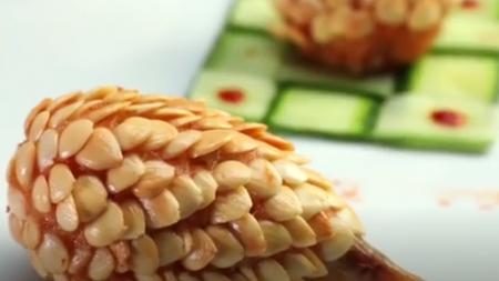 Un homme décore la nourriture d'amandes émincées et crée des formes et des dessins amusants