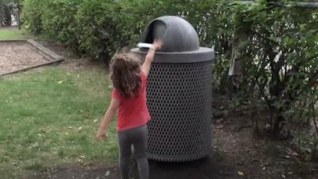 Cette petite fille court vers une poubelle. Mais quand elle jette son déchet, quelque chose d'inattendu saute dehors