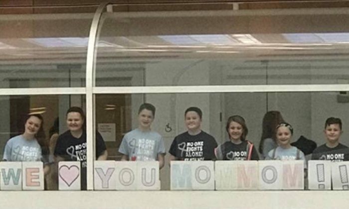 Des enfants interdits d'accès à l'hôpital tiennent une affiche spéciale à l'extérieur de la fenêtre pour leur grand-mère qui se bat contre le cancer
